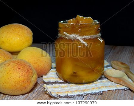 apricot jam in a jar standing on wooden boards that lay next to the apricots