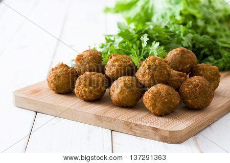 Vegetarian falafels and lettuce on white wooden table