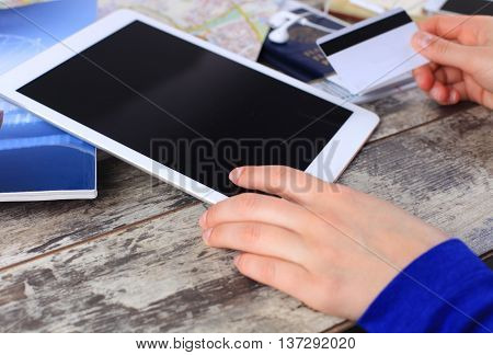 Cropped image of woman using credit card and touchpad for online tour booking on wooden table