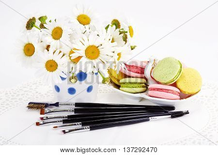 Set of various makeup brushes with flowers and macaroons on white background