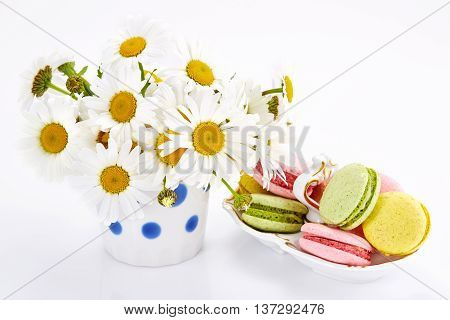Camomiles in vase with macaroons on saucer