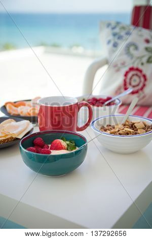 Healthy and delicious breakfast on the balcony with beautiful ocean view. Yogurt with fruit and organic berries cereal and cheese for morning meal. Coffee time. Vacation by the sea.