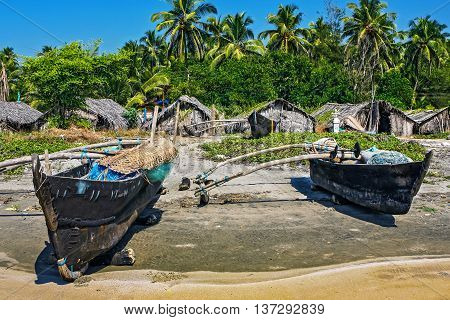 old fishing boat on the beach in tropical with palms huts and blue sky