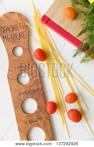 Pasta cooking ingredients and utensils on white table. Cooking spaghetti noodles pasta meal. Wooden measure for pasta.