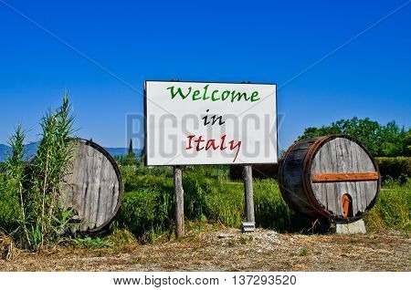 Billboard road surrounded by two wine barrels to welcome the tourists who come to visit Italy