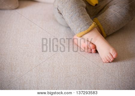 Close up baby legs. Baby feet on the sofa. Barefoot.