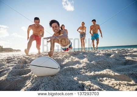 Friends playing rugby at the beach