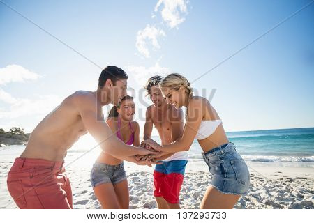 Friends putting their hands together on the beach