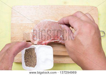 Chef putting salt to raw porkchop / cooking porkchop steak concept