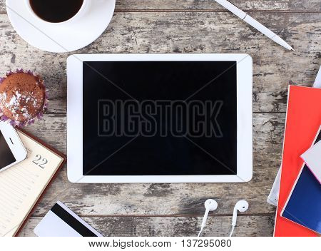 Tablet pc cup of coffee and notepad at wodden table