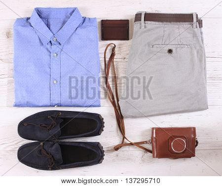 Set of male casual clothing and retro photocamera on wooden background