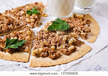 Traditional Asian thin tortilla with minced meat and pine nuts. Selective focus.