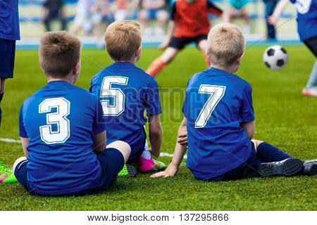Kids of young soccer football team. Boys in blue sport uniforms as reserve players sitting on football pitch and watching soccer match.