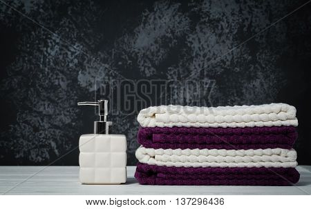Still life white soap dispenser with stacked towels on dark stone background. Closeup with space for text.