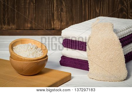 Still life accessories for body care. Close up bath sea salt, massage glove, stacked towels on dark and white wood.