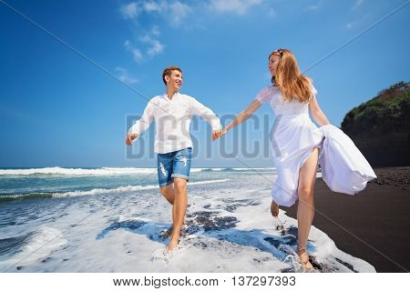 Happy family on honeymoon holiday - just married young man and woman run with fun by black sand beach along sea surf. Active lifestyle people outdoor activity on summer vacation on tropic island.