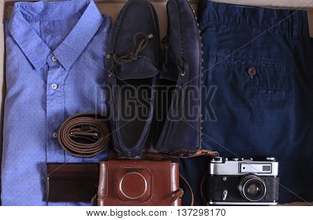 Set of male casual clothing and retro photocamera in a box