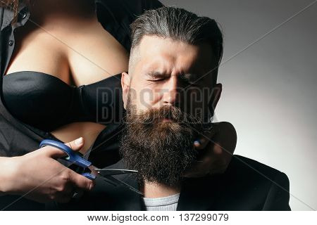 Young handsome man with long beard and moustache on serious face with young woman in bra cutting with scissors