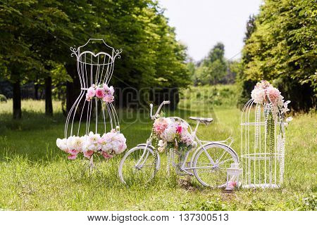 Wedding composition with love stand a white bycicle woman dress shaped stand and flowers