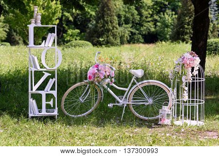 Wedding composition with love stand a white bycicle and flowers