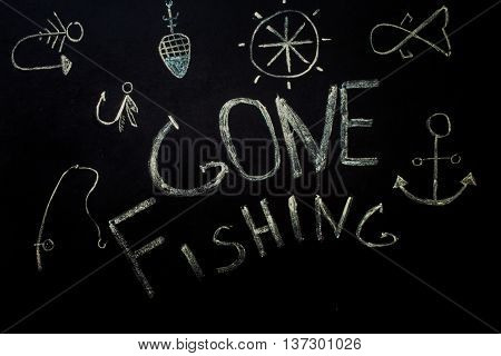 fishinginscription in chalk on a black backgroundfishing accessories