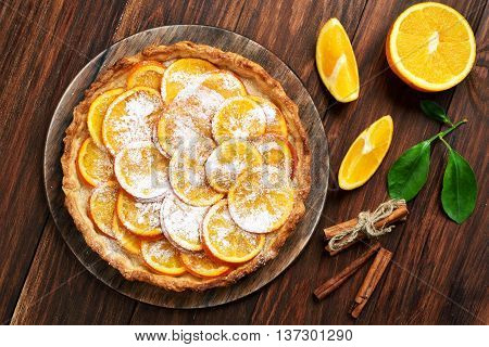 Sweet pie with orange caramelized slices on wooden background top view
