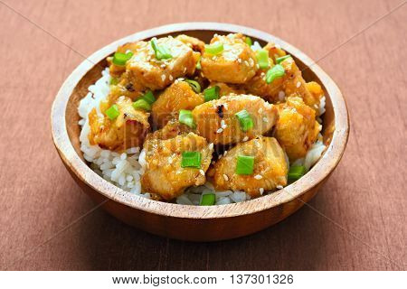 Chicken with orange sauce and rice in wooden bowl
