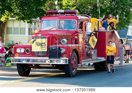 SOUTH ST. PAUL, MINNESOTA - JUNE 24, 2016: Supporters of candidates for city offices in South St. Paul hold banners and wave to crowd from fire truck at annual Kaposia Days Grande Parade on June 24.