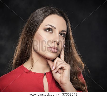 serious young woman pondering over something on a dark background.