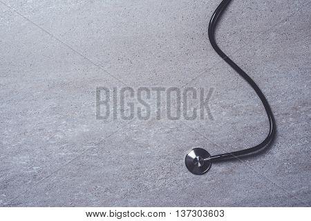 Stethoscope on gray stone background. Close up
