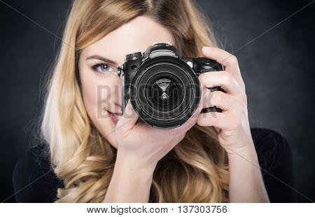 Photographer blond woman holding camera over dark background.