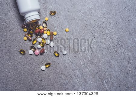 Pill bottle with colorful pills on stone background