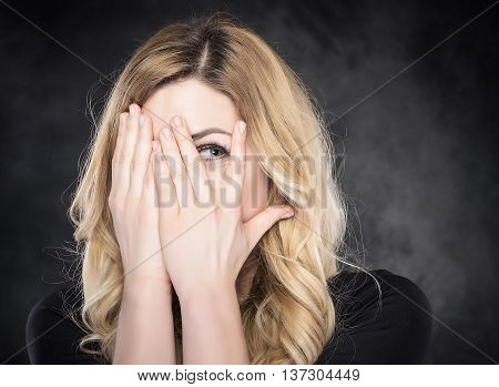 Woman peeping through her fingers over dark background