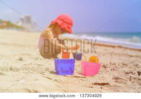 kids toys and little girl building sandcastle on beach