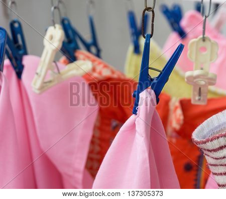 Colorful clothes dry hanging with blue clothes peg on clothesline selective focus