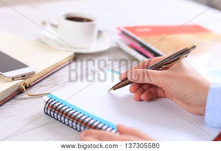 woman's hand makes a note in notebook