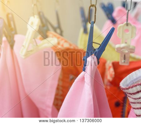 Colorful clothes outdoor dry hanging with blue clothes peg on clothesline with sunlight effect selective focus