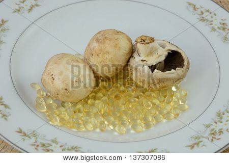 Raw white button mushrooms and vitamin D gel capsules on white plate
