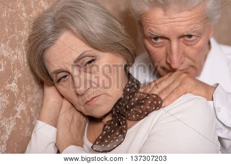 Close-up portrait of sad elder couple at home
