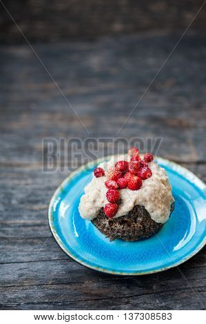 Mini chocolate bundt cake with cream cheese and strawberries on a blue plate