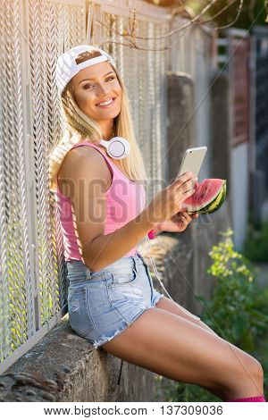 Cheerful blonde happy teenage millennial girl with smartphone, headphones and watermelon outdoors on sunny summer day, sitting, relaxing. Mild retouch, natural lighting.