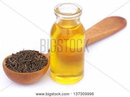 Caraway seeds in a wooden spoon with essential oil in glass bottle