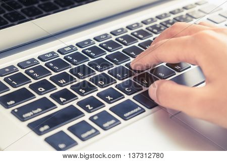 Selective focus on woman hand typing on laptop keyboard in vintage filter tone with warm light effect - business concept of working