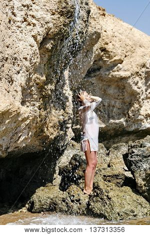 A young woman stands on a rock under a waterfall