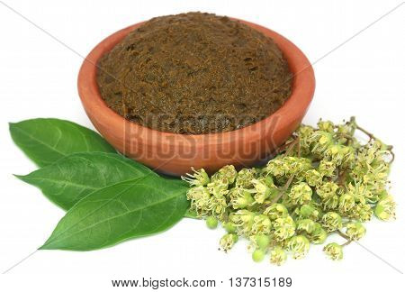 Ayurvedic henna leaves with flowers and paste over white background
