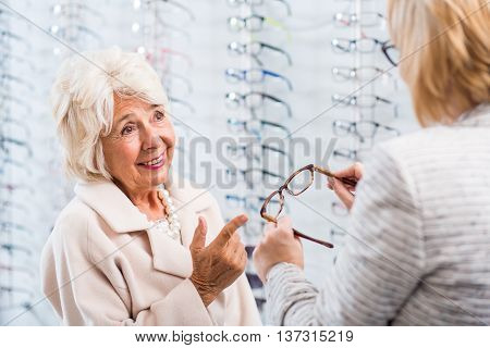 Shop assistant at the optician's showing an old lady a pair of glasses