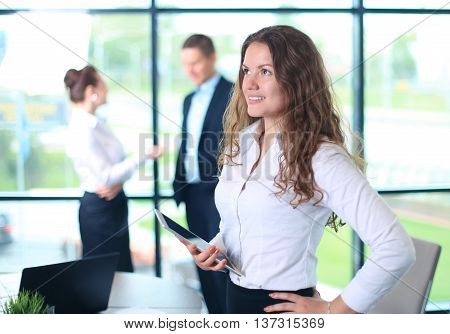 Business woman standing in foreground with a tablet in her hands her co-workers discussing business matters in the background