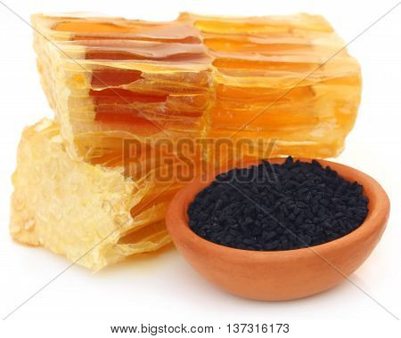 Honey with black cumin in a pottery over white background