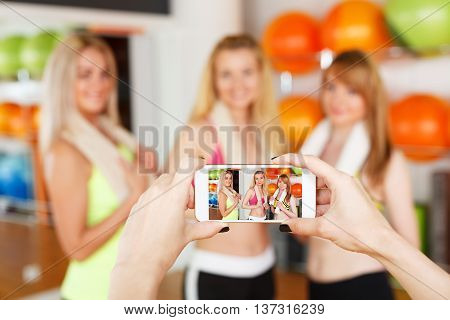 Taking photo of girlfriends. POV image of smartphone screen with girls after fitness training. Portrait of smiling friends at mobile phone, selective focus