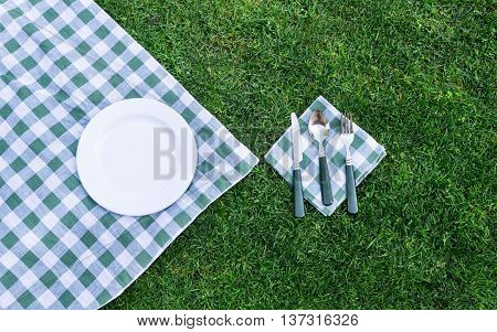 Knife spoon white plate and fork on green picnic tablecloth. Flat lay.